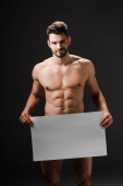 glücklich sexy nackter Mann hält leeres Plakat isoliert auf schwarz