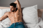 brunette sexy shirtless man in jeans lying on bed on grey