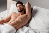 bearded handsome sexy man lying on bed on grey