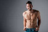 usměvavý svalnatý sexy muž bez trička v džínách na šedé