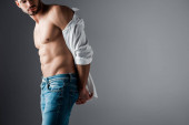 sexy muscular man in white shirt and jeans on grey