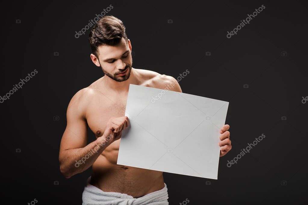 Sexy shirtless man in towel holding blank placard isolated on black stock vector
