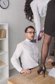 Photo passionate businesswoman standing on desk near shocked colleague and touching his tie