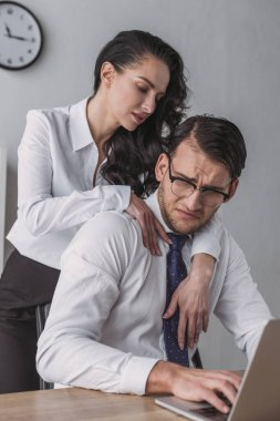 cropped view of seductive businesswoman embracing confused colleague working on laptop