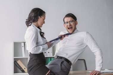 Passionate businesswoman touching tie of shocked colleague while seductive him in office stock vector