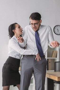 Passionate businesswoman touching trousers of shocked colleague while seductive him in office stock vector