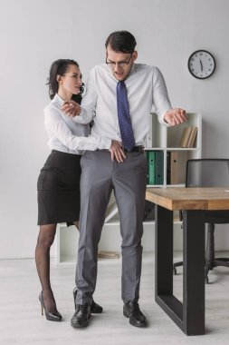 Sexy businesswoman touching trousers of confused colleague while seductive him in office stock vector