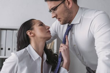 Passionate businesswoman touching tie of confused colleague while seducing him in office stock vector