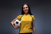 gyönyörű mosolygós fiatal nő kezében labdarúgó labda szürke