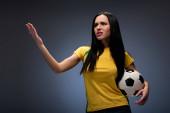 beautiful angry football fan holding ball on grey
