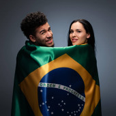 multicultural couple of positive football fans with brazil flag on grey