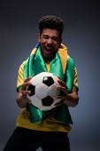 emotional african american man with brazilian flag screaming and holding football ball on grey