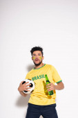 shocked african american man holding football ball and bottle of beer on grey
