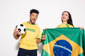 Fotografie multiethnic couple of excited football fans holding brazilian flag, ball and bottle of beer on grey