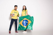 Fotografie multiethnic couple of surprised football fans holding brazilian flag, ball and bottle of beer on grey