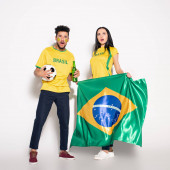 multiethnic couple of shocked football fans holding brazilian flag, ball and bottle of beer on grey