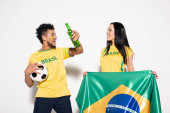 multicultural couple of happy football fans holding brazilian flag, ball and bottle of beer on grey