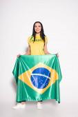 smiling female football fan holding brazilian flag on grey