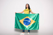attractive smiling female football fan holding brazilian flag on grey