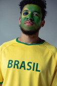 african american football fan with face painted as brazilian flag isolated on grey