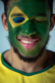 smiling african american football fan with closed eyes and face painted as brazilian flag isolated on grey