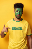 serious african american football fan with painted face pointing at t-shirt with brazil sign on yellow