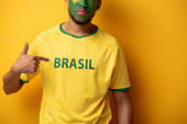 cropped view of football fan with painted face pointing at t-shirt with brazil sign on yellow