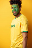 handsome african american football fan with face painted as brazilian flag on yellow