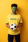 african american football fan with face painted as brazilian flag holding ball on yellow
