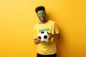 excited african american football fan with face painted as brazilian flag holding ball on yellow