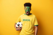 Fotografie emotional african american football fan with face painted as brazilian flag yelling and holding ball on yellow
