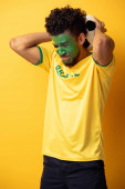 crying african american football fan with face painted as brazilian flag holding ball on yellow