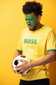 stressed african american football fan with face painted as brazilian flag holding ball on yellow