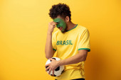 confused african american football fan with face painted as brazilian flag holding ball on yellow
