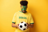 sad african american football fan with face painted as brazilian flag holding ball on yellow
