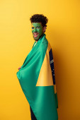 excited african american football fan with painted face wrapped in brazilian flag on yellow