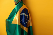 cropped view of football fan with painted face wrapped in brazilian flag on yellow