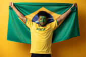 african american football fan with painted face holding brazilian flag on yellow