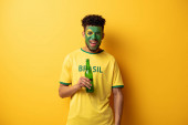 cheerful african american football fan with face painted as brazilian flag holding bottle of beer on yellow