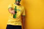 cropped view of african american football fan with face painted as brazilian flag holding bottle of beer on yellow