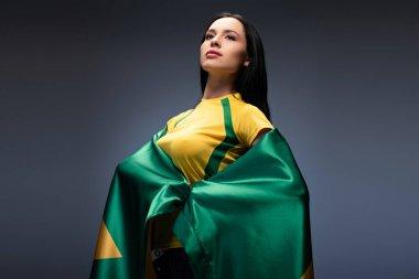 attractive proud female football fan wrapped in brazilian flag on grey