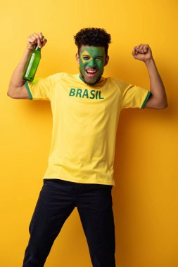 excited african american football fan with face painted as brazilian flag holding bottle of beer on yellow