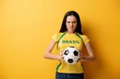 aggressive female football fan holding ball on yellow