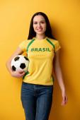 mosolygó női labdarúgó fan holding ball sárga