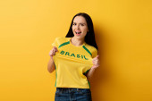 excited female football fan in yellow t-shirt with brazil sign on yellow