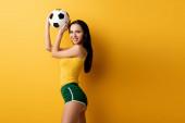 Fotografie usmívající se ženský fotbalový fanoušek v trenýrkách drží míč na žluté