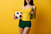 cropped view of female football fan holding ball and bottle of beer on yellow