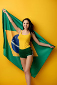 Photo cheerful female football fan in shorts holding brazilian flag on yellow