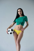 Photo beautiful sensual girl posing with football ball isolated on grey