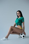 Photo attractive seductive football fan posing with ball on grey